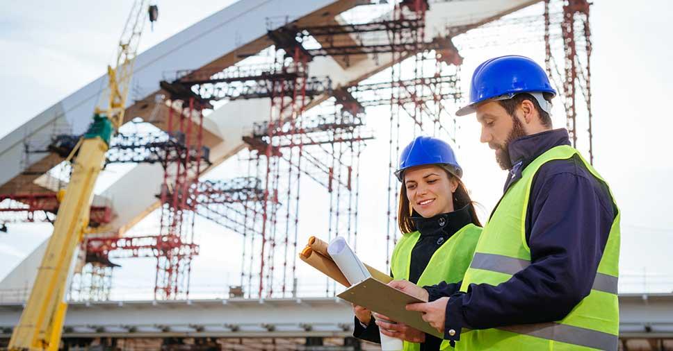 Dois engenheiros de uma empresa de construção civil trabalhando no canteiro de obras