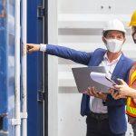 dois engenheiros equipados com capacete, máscara tendo ajuda da prancheta e notebook para fazer a gestão de obras