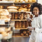 funcionária sorridente após saber como montar uma padaria de sucesso